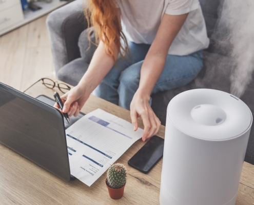 Woman freelancer uses a household humidifier in the workplace to maintain relative humidity and microclimate in the workplace of the home office with a laptop and documents.