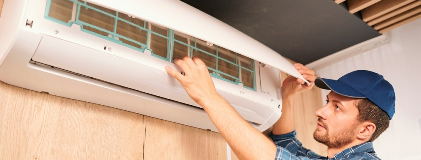 Young household technician opening lid of air conditioner to check what is wrong with it while doing his work