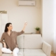 Domestic Life, Climate Control. Happy woman switching on air conditioner while sitting on couch, copyspace